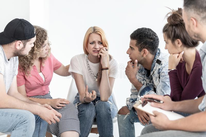 Młodzi ludzie wspiera płacz nastoletniej dziewczyny podczas spotkania z terapeuta obrazy royalty free
