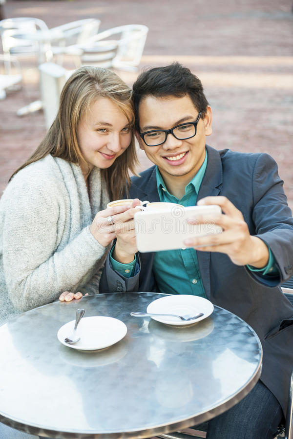 Młodzi ludzie z smartphone w kawiarni zdjęcie royalty free