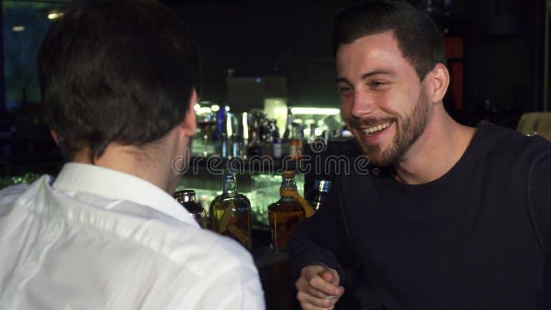 Młodzi męscy przyjaciele opowiada podczas gdy mieć napój przy barem wpólnie obraz stock