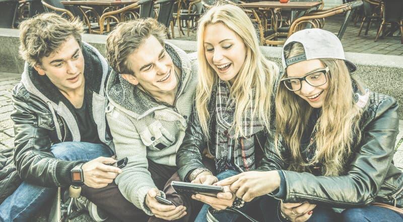 Młodzi miastowi przyjaciele ma zabawę wpólnie używa mobilnego mądrze telefon obraz royalty free