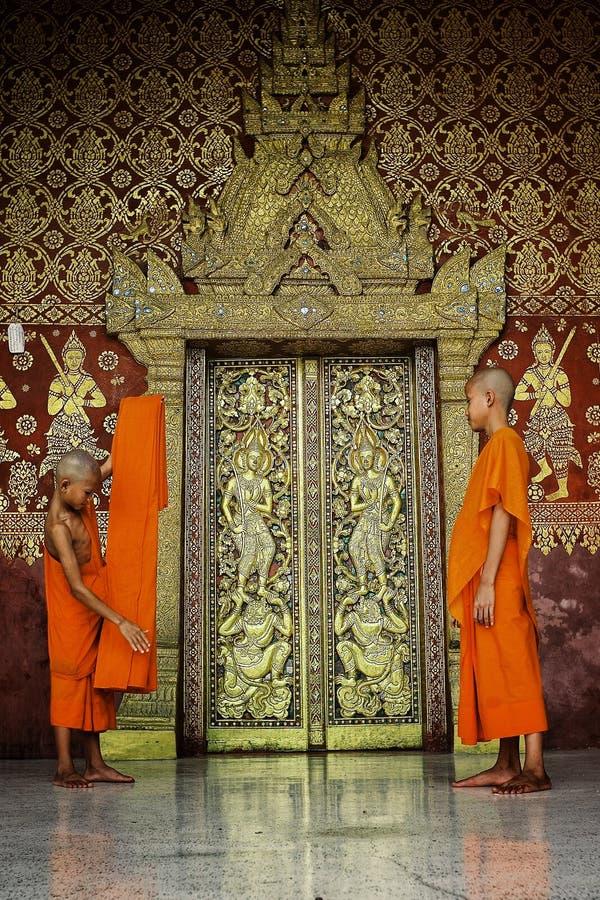 młodzi mnisi buddyjscy składa pomarańczową tkaninę przed miło dekorującym złotym matrycującym drewnianym drzwi zdjęcie royalty free