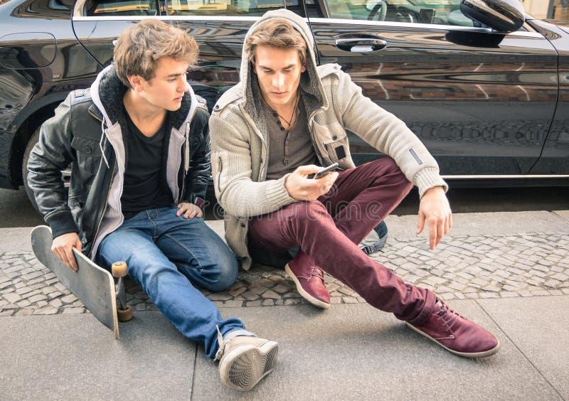 Młodzi modniś mody bracia ma zabawę z smartphone fotografia royalty free