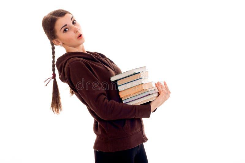 Młodzi nastoletni stojaki z ukosa i chwyty wiele książki fotografia royalty free