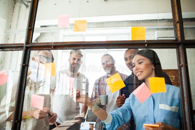 Młodzi nowożytni ludzie w mądrze przypadkowej odzieży używać adhezyjne notatki w deskowym pokoju podczas gdy stojący za szklaną ś obrazy royalty free