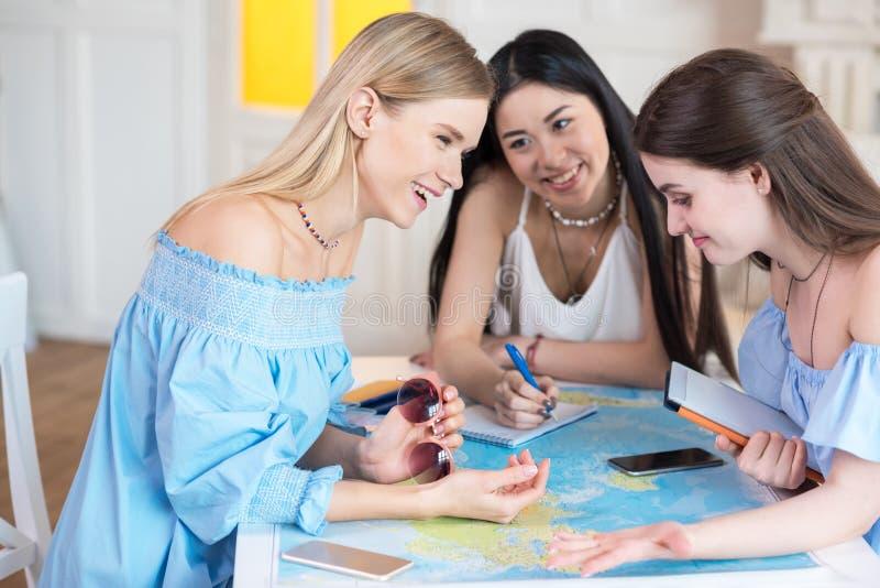 młodzi piękni kobieta podróżnicy patrzeje światową mapę przy izbowym best fotografia stock