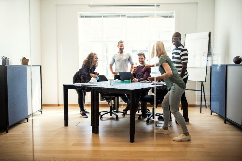 Młodzi projektanci śmia się stołowego tenisa i bawić się podczas ich b obraz stock