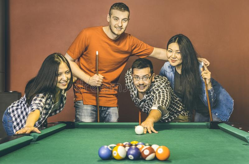 Młodzi przyjaciele bawić się basenu przy bilardowego stołu barem - Szczęśliwa przyjaźń obraz stock