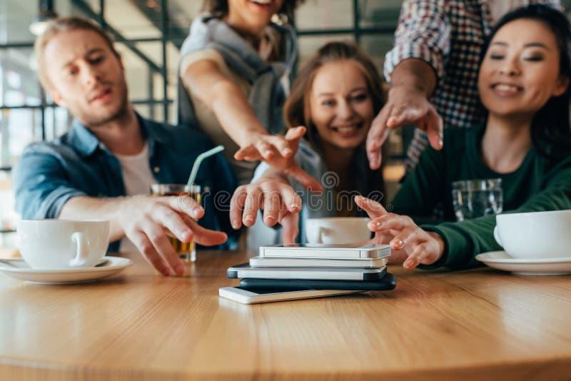 Młodzi przyjaciele bierze z powrotem ich smartphones kłama w stosie na stole obraz stock