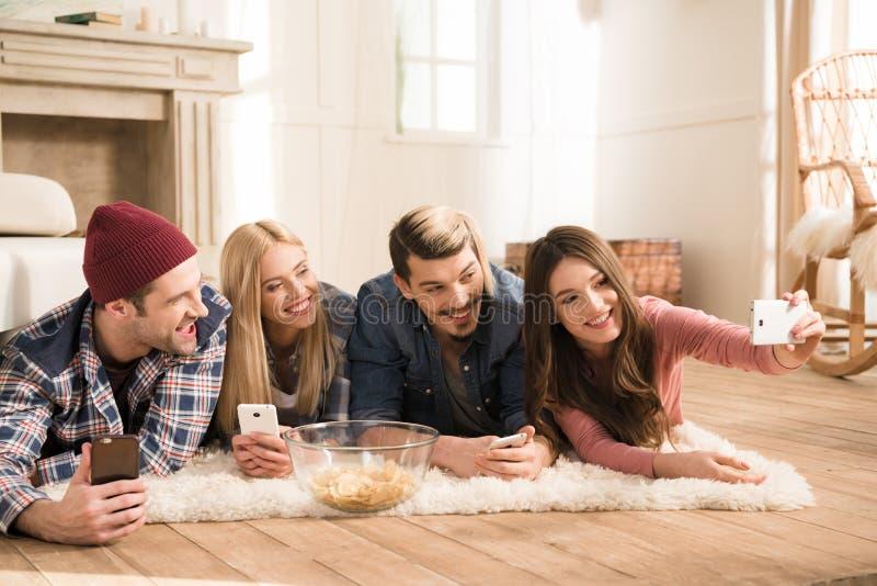 Młodzi przyjaciele kłama na dywanie i bierze selfie w domu obraz stock