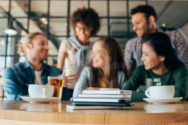 Młodzi przyjaciele kłama w stosie na stole przy stołem w kawiarni ich smartphones fotografia stock