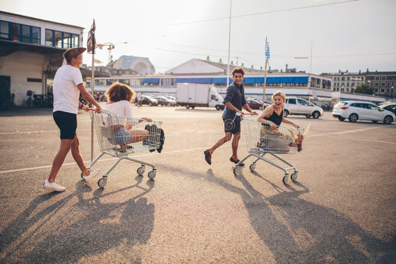 Młodzi przyjaciele ma zabawę na wózek na zakupy obraz royalty free