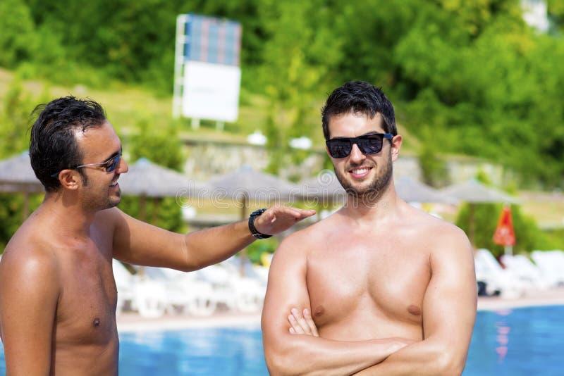 Młodzi przyjaciele opowiada zabawę na basenie i ma fotografia royalty free