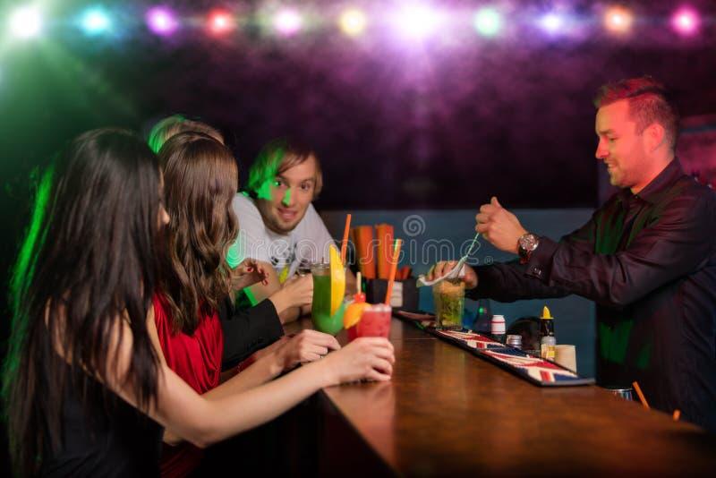 Młodzi przyjaciele pije koktajle wpólnie przy przyjęciem obrazy royalty free