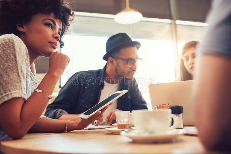Młodzi przyjaciele przy sklep z kawą z laptopem i cyfrową pastylką obrazy stock