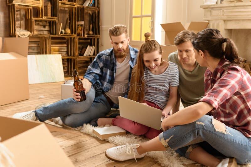 Młodzi przyjaciele siedzi na dywanie i używa laptop w nowym domu obrazy royalty free