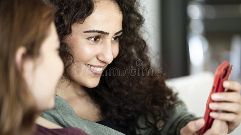 Młodzi przyjaciele używa telefon komórkowego w domu fotografia stock