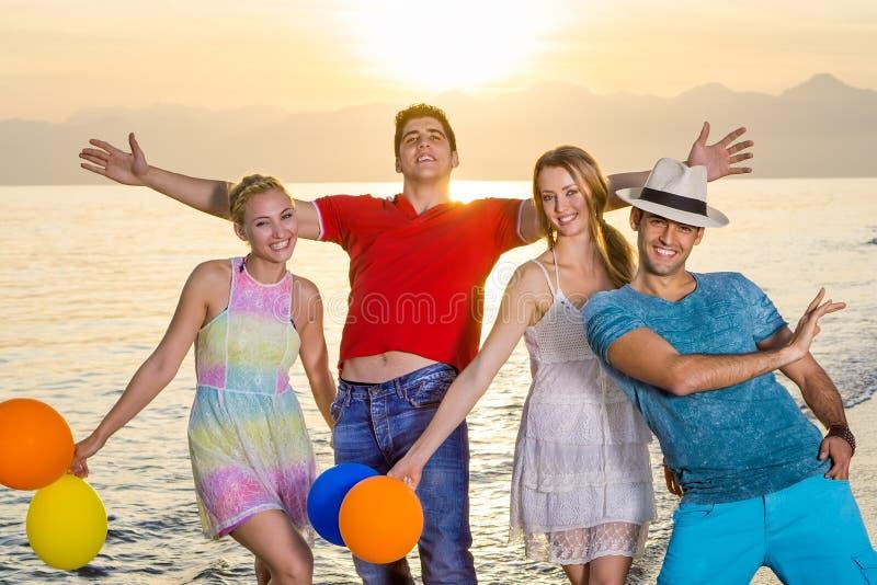 Młodzi przyjaciele w Przypadkowych Szczęśliwych pozach przy plażą obraz royalty free