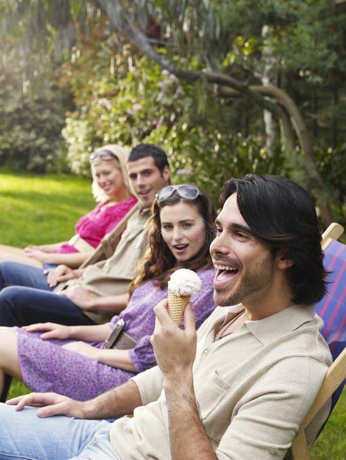 Młodzi przyjaciele W rzędzie Na Deckchairs Przy ogródem obraz royalty free