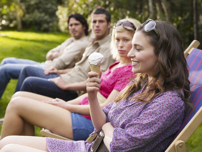 Młodzi przyjaciele W rzędzie Na Deckchairs Przy ogródem zdjęcia royalty free