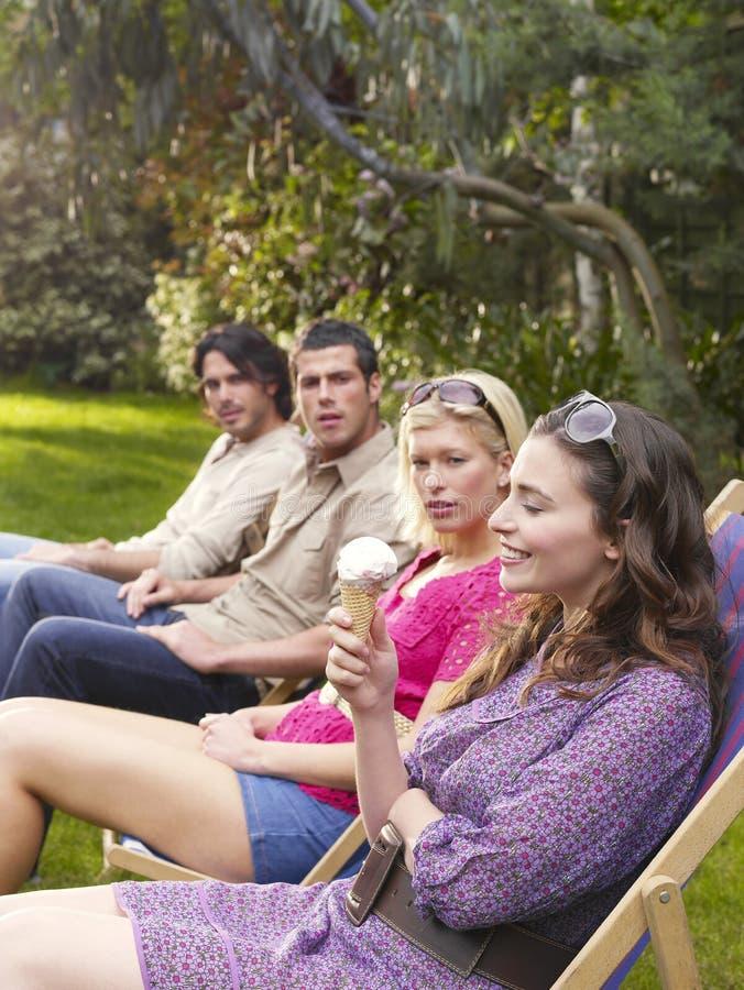 Młodzi przyjaciele W rzędzie Na Deckchairs Przy ogródem obrazy royalty free