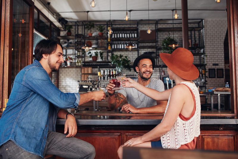 Młodzi przyjaciele wznosi toast napoje przy kawiarnią zdjęcie royalty free
