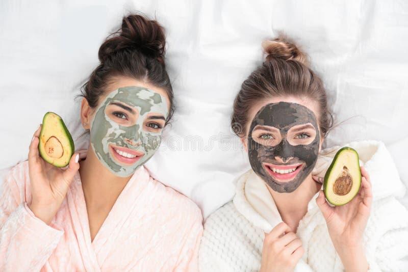 Młodzi przyjaciele z twarzowymi maskami ma zabawę na łóżku przy pamper przyjęcia zdjęcia royalty free