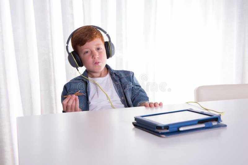 Młodzi redhaired chłopiec ist słucha z hełmofonami obraz stock