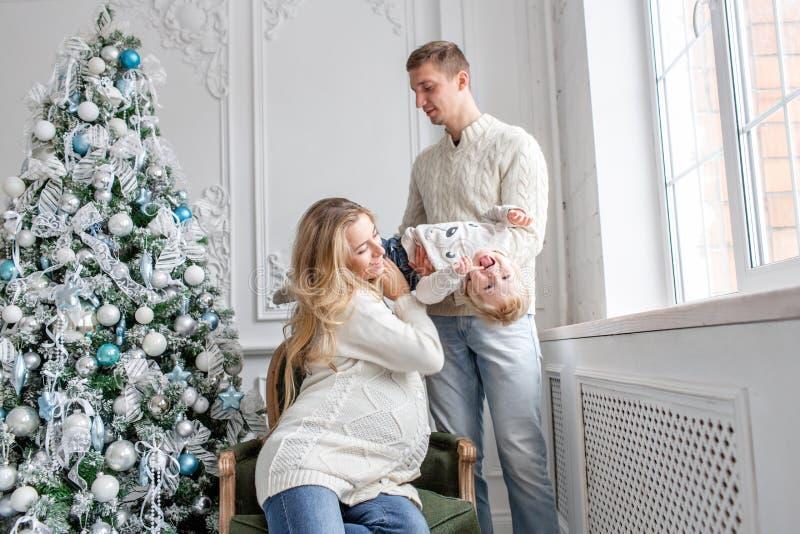 Młodzi rodzice błaź się wokoło i bawić się z małym synem szczęśliwa rodzinna zabawa mieć domowego Poranek bożonarodzeniowy w jask zdjęcie royalty free