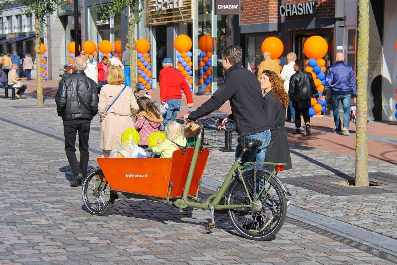 Młodzi rodzice niosą dzieci w rowerowym spacerowiczu fotografia royalty free