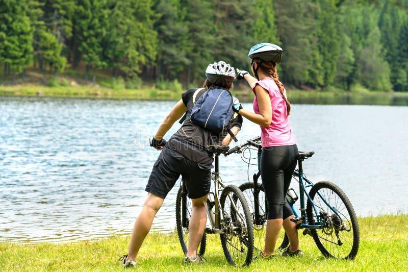 Młodzi rowerzyści ogląda las przy jeziorem obraz stock