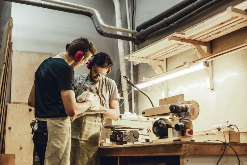 Młodzi rzemieślnicy projektuje blisko workbench obrazy royalty free