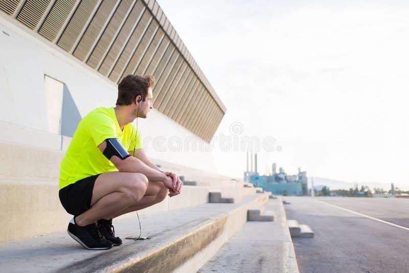 Młodzi sporty obsługują rozważny patrzeć oddaleni podczas gdy mieć odpoczynek po treningu trenuje outdoors w miastowym położeniu fotografia stock