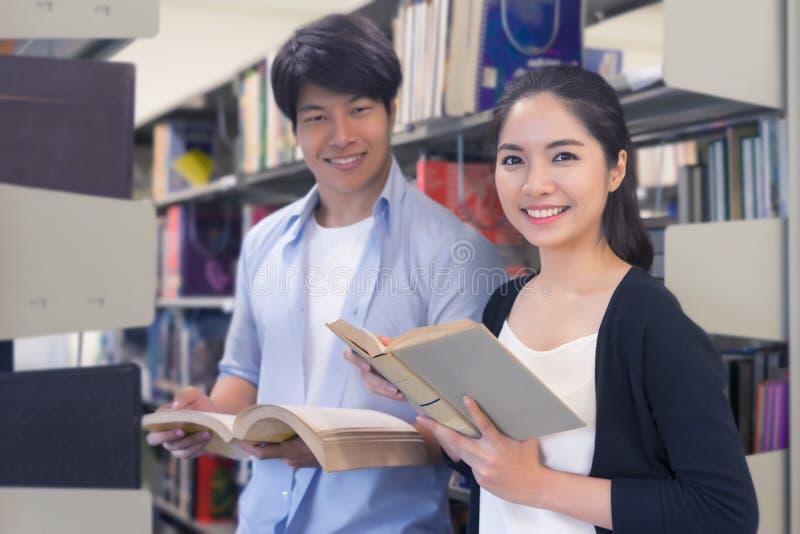 Młodzi student collegu czyta książkę wpólnie w bibliotece Educa obrazy royalty free