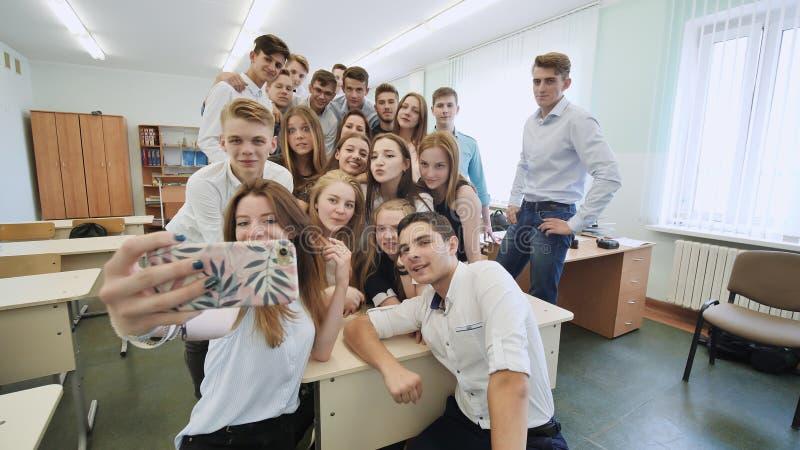 Młodzi szczęśliwi rozochoceni ucznie robi selfie w szkolnej klasie zdjęcie stock