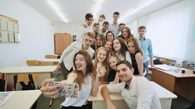 Młodzi szczęśliwi rozochoceni ucznie robi selfie w szkolnej klasie obrazy stock