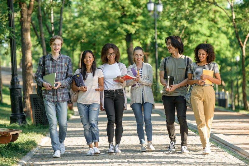 Młodzi szczęśliwi ucznie chodzi podczas gdy opowiadający przyglądając się na bok obrazy royalty free