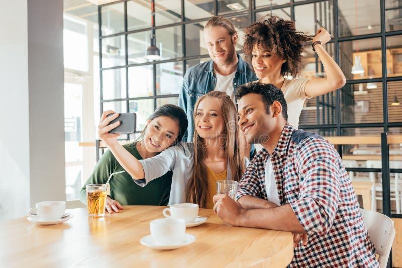 Młodzi szczęśliwi wieloetniczni przyjaciele bierze selfie obraz royalty free