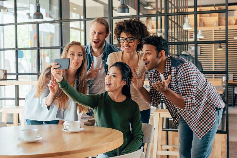 Młodzi szczęśliwi wieloetniczni przyjaciele bierze selfie zdjęcie stock