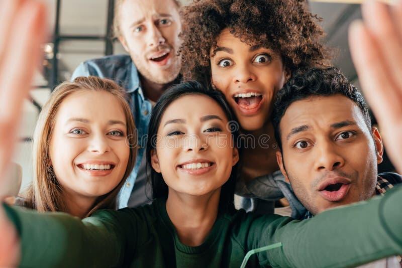 Młodzi szczęśliwi wieloetniczni przyjaciele bierze selfie zdjęcia stock