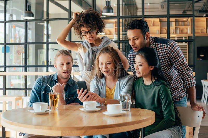 Młodzi szczęśliwi wieloetniczni przyjaciele patrzeje smartphone podczas gdy odpoczywający fotografia royalty free