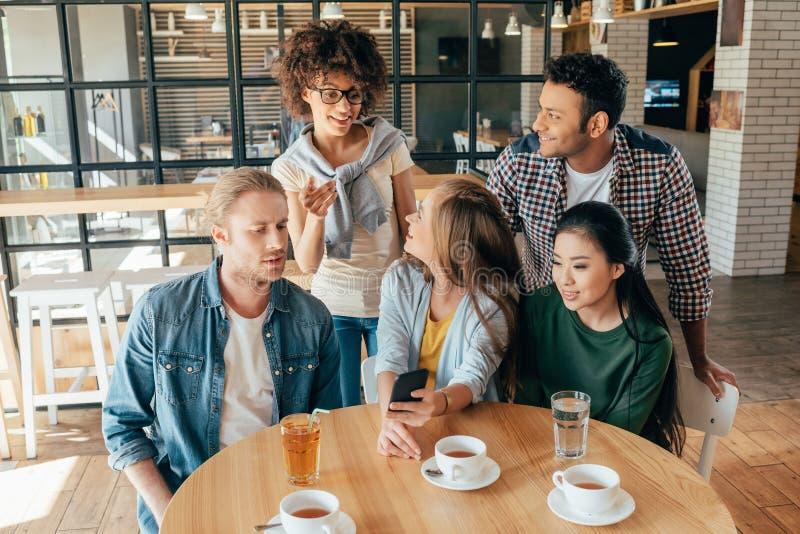 Młodzi szczęśliwi wieloetniczni przyjaciele patrzeje smartphone podczas gdy odpoczywający zdjęcie stock