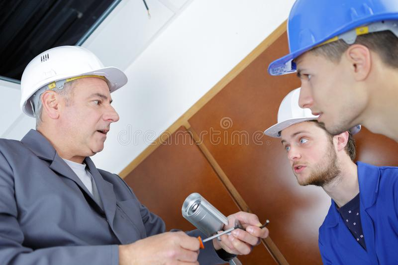 Młodzi technicy uczy się instalować kamerę w budynku osaczają zdjęcia royalty free