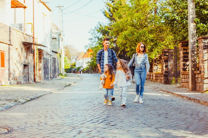 Młodzi turyści z ich córkami chodzi puszek ulica obrazy stock