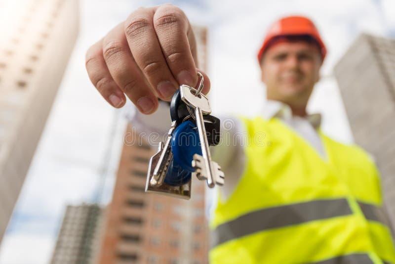 Młodzi uśmiechnięci budowa inżyniera mienia klucze od nowego domu fotografia stock