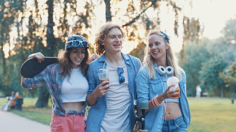 Młodzi uśmiechnięci deskorolkarze w parku obrazy royalty free