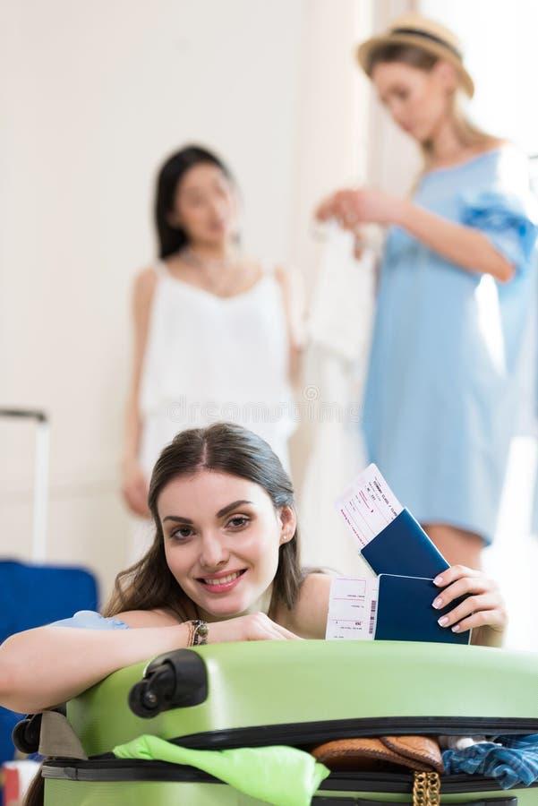 Młodzi uśmiechnięci kobiety mienia paszporty i bilety podczas gdy przyjaciele pakuje walizkę za dostawać przygotowywający obrazy royalty free
