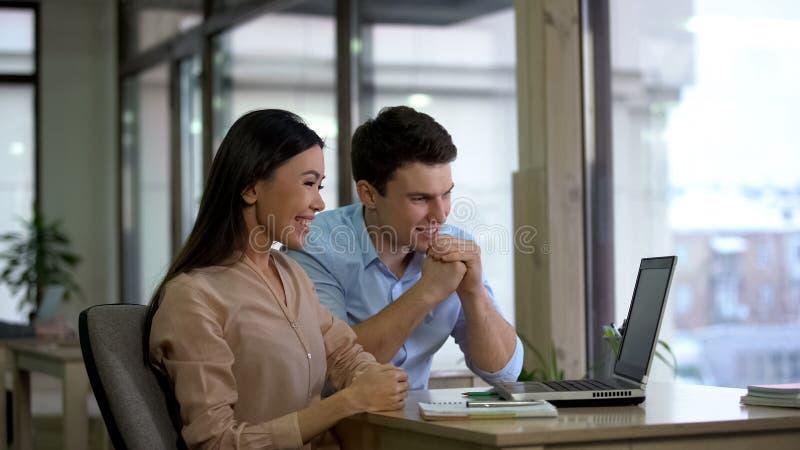 Młodzi uśmiechnięci koledzy patrzeje laptop wpólnie siedzi biuro stół, praca zespołowa zdjęcie stock