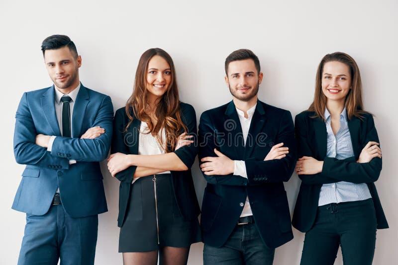 Młodzi uśmiechnięci ludzie biznesu z ręka krzyżującym chudy ściana w biurze fotografia royalty free