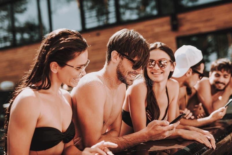 Młodzi Uśmiechnięci przyjaciele używa Smartphone przy Poolside obrazy stock