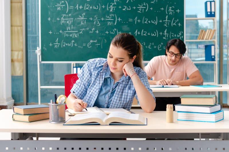 Młodzi ucznie bierze matematyka egzamin w sali lekcyjnej obrazy stock